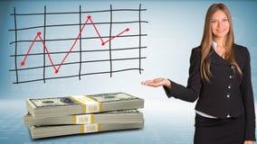 Bizneswomanów punktów ręka na paczka dolarach Zdjęcie Stock