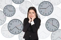 Bizneswomanów stojaki wśród zegarów Obraz Royalty Free