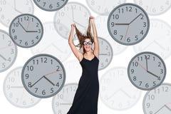 Bizneswomanów stojaki wśród zegarów Zdjęcie Stock