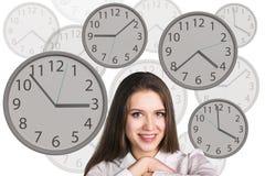 Bizneswomanów stojaki wśród zegarów Fotografia Royalty Free