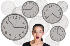 Bizneswomanów stojaki wśród zegarów Obrazy Stock