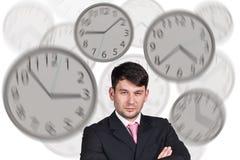 Bizneswomanów stojaki wśród zegarów Obraz Stock