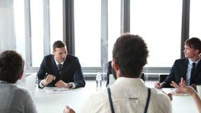 Bizneswoman daje prezentaci, coleaguess siedzi przy stołowym i klaskać, zdjęcie wideo
