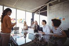 Bizneswoman daje prezentaci koledzy w biurze fotografia stock
