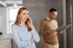 Bizneswoman dzwoni na smartphone przy biurem Obrazy Stock