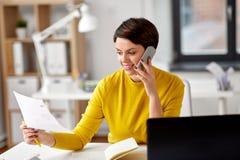Bizneswoman dzwoni na smartphone przy biurem fotografia stock