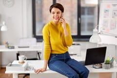 Bizneswoman dzwoni na smartphone przy biurem zdjęcia royalty free
