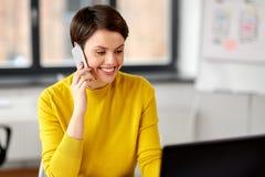 Bizneswoman dzwoni na smartphone przy biurem obraz stock