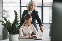 Bizneswoman i jej szef pracuje z laptopem w biurze obrazy stock
