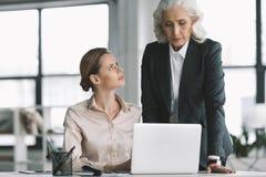 Bizneswoman i jej szef pracuje z laptopem w biurze obraz stock