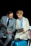 Bizneswoman i w średnim wieku biznesmen z pastylką gazetową i cyfrową zdjęcie royalty free
