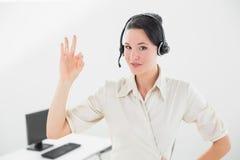 Bizneswoman jest ubranym słuchawki podczas gdy gestykulujący ok podpisuje wewnątrz biuro Obrazy Stock