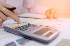 Bizneswoman kalkuluje o koszcie i mapy donoszą na stole, kalkulator na biurku pieniężny heblowanie kalkulatorów pojęć finansowy p Zdjęcia Royalty Free