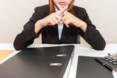 Bizneswoman mówi dalej przy jej biurem nie z przecinającymi palcami obrazy stock