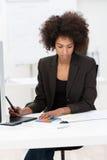 Bizneswoman mocno przy pracą przy jej biurkiem fotografia royalty free