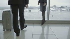 Bizneswoman na szpilkach z biznesmenem z bagażem blisko okno w lotnisku zdjęcie wideo