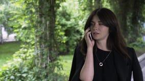 Bizneswoman na telefonu odprowadzeniu w parku zbiory