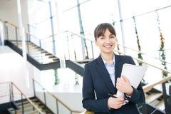 Bizneswoman ono Uśmiecha się Podczas gdy Trzymający dokument Przeciw schodom obrazy stock