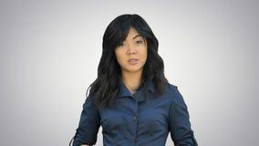 Bizneswoman ono uśmiecha się wyjaśnia z gestem na białym tle w błękitnym kostiumu patrzejący kamerę Fotografia Royalty Free