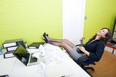 Bizneswoman opiera przy jej biurkiem bawić się ukulele Obraz Stock