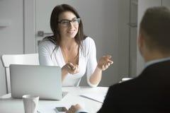 Bizneswoman opowiada mężczyzna przy biurkiem Fotografia Royalty Free