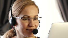 Bizneswoman opowiada na słuchawki w biurze obsługi klienta proffessional 4K zdjęcie wideo