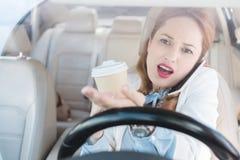 bizneswoman opowiada na smartphone z filiżanka kawy w ręce podczas gdy obraz stock