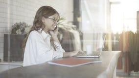 Bizneswoman opowiada na telefonie i pisać na maszynie zamazanym tle Obrazy Royalty Free