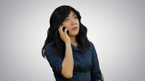 Bizneswoman opowiada na telefonie komórkowym na białym tle w błękitnym kostiumu zdjęcie royalty free