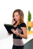 Bizneswoman opowiada na telefonie w biurze i trzyma pastylkę z listą zadania Biznesowy pojęcie biurowa praca Zdjęcia Royalty Free