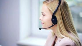 Bizneswoman opowiada przy biurem z słuchawki zbiory wideo