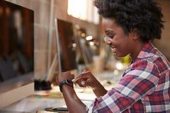 Bizneswoman Patrzeje Mądrze zegarek W projekta biurze Zdjęcie Stock