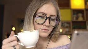 Bizneswoman pije kawę w kawiarni z smartphone zbiory wideo