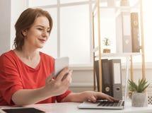 Bizneswoman pisać na maszynie na laptopie i używa smartphone w biurze Zdjęcie Royalty Free