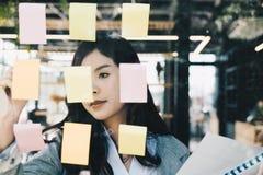 Bizneswoman pisze na adhezyjnych notatkach na szklanej ścianie w spotykać r zdjęcia royalty free