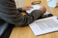 bizneswoman pisze notatce podczas gdy przeglądający kontrakt kobiety conside zdjęcia royalty free