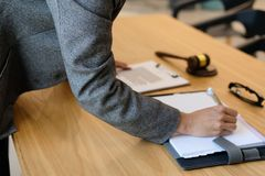 bizneswoman pisze notatce podczas gdy przeglądający kontrakt kobiety conside zdjęcia stock
