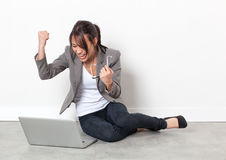Bizneswoman podnosi jej pięści dla sukcesu relaksuje na podłoga Fotografia Stock