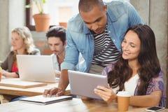 Bizneswoman pokazuje cyfrową pastylkę męski kolega Obrazy Stock