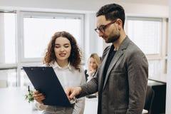Bizneswoman pokazuje jej koledze coś na jej pastylka komputerze zdjęcie stock