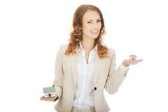 Bizneswoman porównuje dwa domowego modela obrazy stock