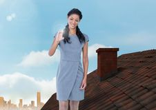Bizneswoman pozycja na dachu z kominem i miasta niebem Zdjęcie Stock