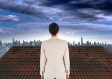 Bizneswoman pozycja na dachu z miasta niebem Zdjęcia Stock