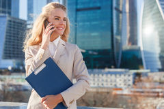 Bizneswoman pozycja przed drapaczami chmur i opowiadać na telefonie Zdjęcia Stock
