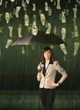 Bizneswoman pozycja z parasolem w dolarowego rachunku deszczu pojęciu Obrazy Royalty Free