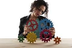 Bizneswoman próby łączyć przekładnia kawałki Pojęcie praca zespołowa, partnerstwo i integracja, zdjęcia royalty free