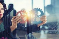 Bizneswoman próby łączyć przekładnia kawałki Pojęcie praca zespołowa, partnerstwo i integracja, podwójny narażenia zdjęcie stock