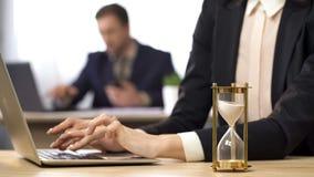 Bizneswoman pracuje na komputerze, hourglass ciurkanie, wynik antycypacja zdjęcie royalty free