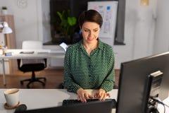 Bizneswoman pracuje na komputerze przy nocy biurem obraz stock