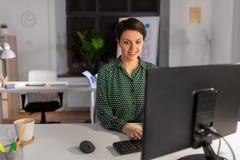 Bizneswoman pracuje na komputerze przy nocy biurem fotografia royalty free